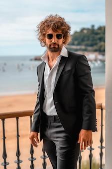 Estilo de rua com um jovem homem caucasiano de cabelos escuros em um terno preto e uma camisa branca em um hotel de luxo, com óculos de sol, editorial de moda. modelo empoleirado na janela