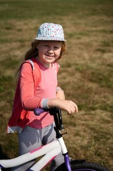 Estilo de vida ativo de crianças modernas, linda garota loira passeia com uma bicicleta no campo