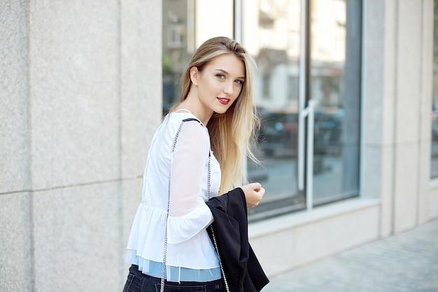 Estilo de vida ativo de uma jovem loira linda aluna na camisa branca e calça preta andando na rua