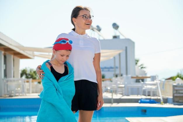 Estilo de vida ativo e saudável, mãe e filha com chapéu esportivo e óculos para nadar com toalha perto da piscina ao ar livre
