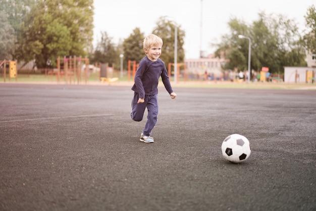 Estilo de vida ativo em uma cidade moderna - garoto jogando com uma bola de futebol no estádio