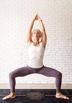 Estilo de vida ativo. jovem mulher atraente vestindo roupas esportivas, praticando ioga em casa. fundo de parede de tijolo branco, comprimento total interno. t-shirt simulada