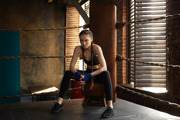 Estilo de vida ativo saudável, conceito de determinação e resistência. jovem lutadora confiante usando bandagens e roupas esportivas, fazendo uma pausa durante o treinamento