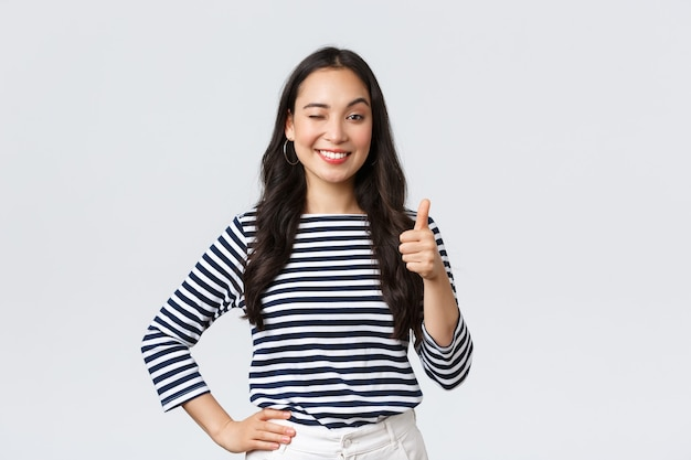 Estilo de vida, beleza e moda, conceito de emoções de pessoas. alegre fofa garota asiática com polegar para cima em aprovação, piscadela encorajando e sorrindo, elogiando o bom trabalho, diga bem jogado e parabenize com a vitória