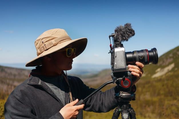 Estilo de vida close-up fotógrafo de viagens homem de chapéu bege com câmera