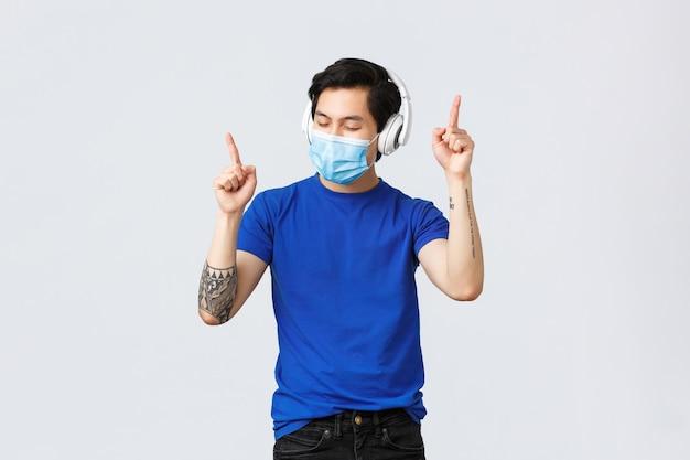 Estilo de vida covid-19, emoções das pessoas e lazer no conceito de quarentena. hipster asiático despreocupado e bonito em máscara médica, dançando a música favorita em fones de ouvido, ouvindo música