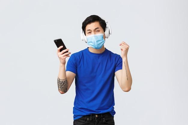 Estilo de vida covid-19, emoções das pessoas e lazer no conceito de quarentena. homem asiático engraçado e despreocupado curtindo batidas em novos fones de ouvido, segurando um telefone celular, usando máscara médica e dançando