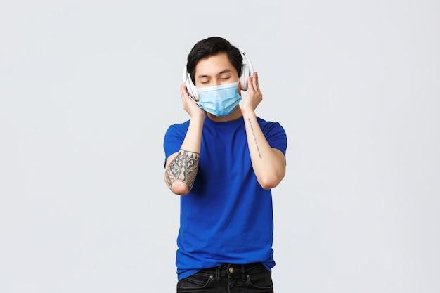 Estilo de vida covid-19, emoções das pessoas e lazer no conceito de quarentena. homem asiático feliz despreocupado relaxando com a música favorita em fones de ouvido, feche os olhos e sorria na máscara médica.