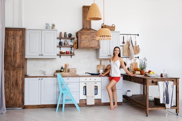 Estilo de vida da linda garota de pé junto ao fogão na cozinha, cozinhando e cheirando bons aromas de fritura de alimentos
