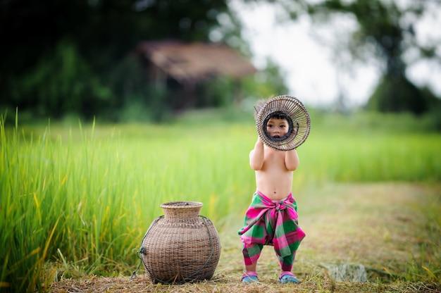 Estilo de vida de bebê tailandês fora porta na natureza