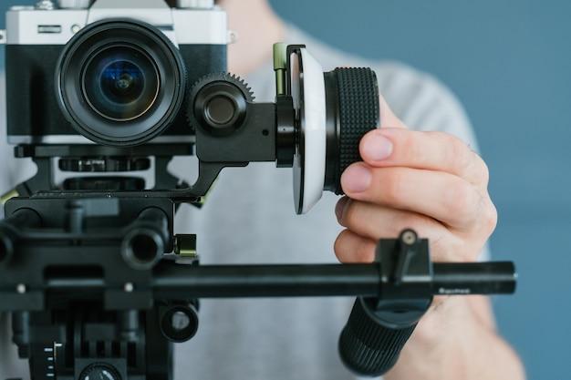 Estilo de vida de cameraman e hobby de filmagem. homem criando conteúdo para transmissão ou blog usando a câmera no suporte e um tripé. conceito moderno de equipamentos e ferramentas.