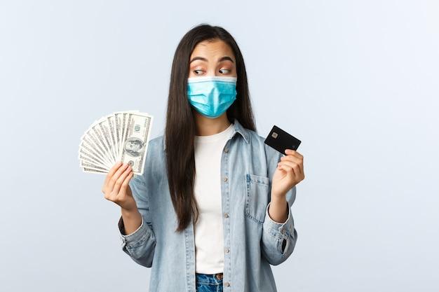 Estilo de vida de distanciamento social, negócio pandêmico covid-19 e conceito de emprego. menina asiática com máscara médica toma a decisão entre dinheiro e cartão de crédito, prefere pagar com dinheiro.
