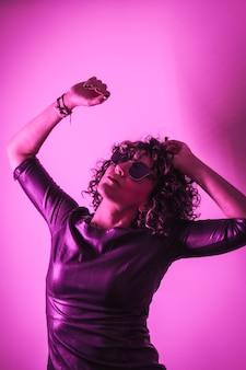 Estilo de vida de estúdio, uma jovem mulher caucasiana olhando para uma sessão de fotos com roupas elegantes e óculos de sol, com luz neon rosa