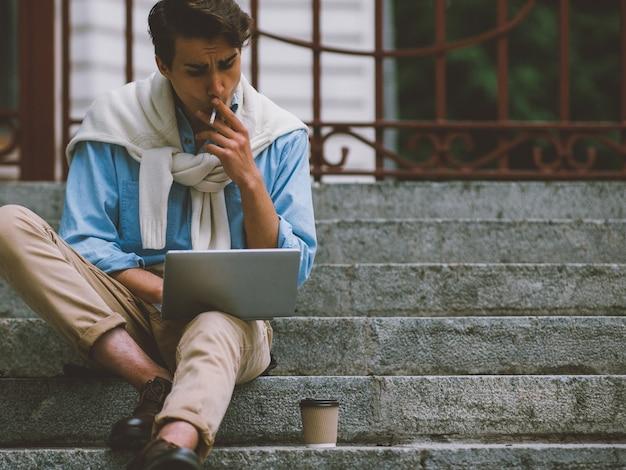 Estilo de vida de freelancer. tecnologia moderna. cara metrossexual sentado na escada trabalhando em fumar laptop.