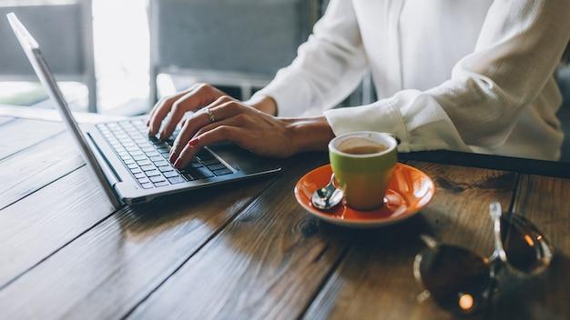 Estilo de vida de freelancer. trabalho remoto. gerente feminina trabalhando no laptop no café.