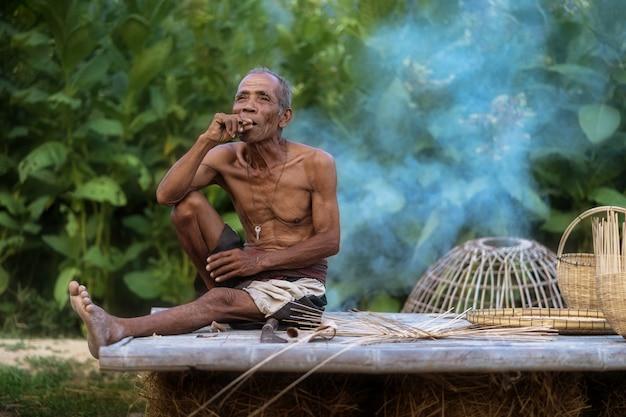 Estilo de vida de homem idoso dos habitantes locais com bambu de ofício