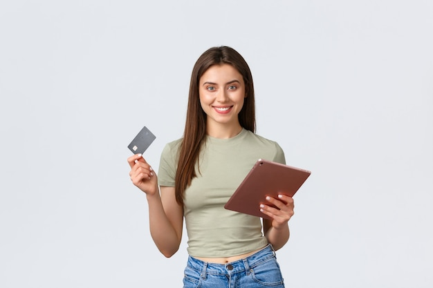Estilo de vida de moda e beleza e conceito de compras sorrindo bem parecida garota cliente feminina fazendo pedidos online com cartão de crédito e loja de tablet digital na parede branca da internet