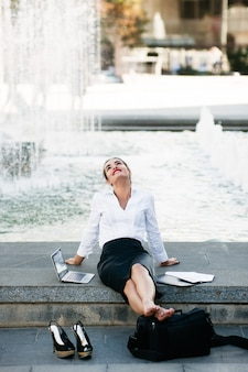 Estilo de vida de mulher de negócios urbana de conteúdo descontraído trabalhando ao ar livre