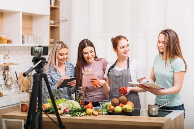 Estilo de vida de nutrição saudável. blogging. mulheres jovens animadas escrevendo receita. gravação de vídeo em smartphone.