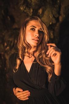 Estilo de vida de uma jovem loira caucasiana em um vestido preto dentro de uma caverna iluminada com luz amarela