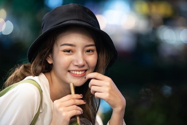 Estilo de vida de viagem da menina asiática com copo de água potável em quase