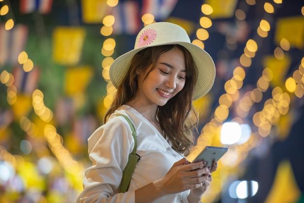 Estilo de vida de viagem da menina asiática com smartphone à noite