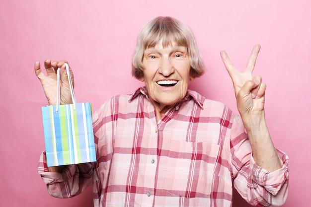 Estilo de vida e as pessoas: feliz mulher sênior com sacola de compras sobre rosa