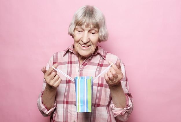 Estilo de vida e conceito de pessoas: feliz mulher sênior com sacola de compras