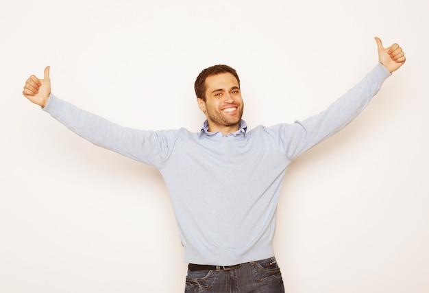 Estilo de vida e conceito de pessoas: jovem casual em uma camisa com as duas mãos levantadas no ar. vencedor e feliz.