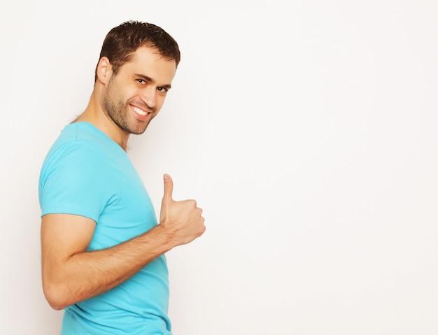 Estilo de vida e conceito de pessoas: jovem feliz de camisa azul mostrando os polegares para cima