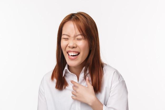 Estilo de vida e conceito de pessoas. retrato do close-up da menina asiática engraçada despreocupada, rindo em voz alta com um sorriso radiante e os olhos fechados, toque a risada no peito de piadas hilariantes na parede branca