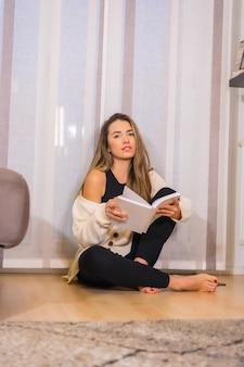 Estilo de vida em casa, jovem loira caucasiana com um café sorrindo, lendo um livro na sala de estar, sentada no chão