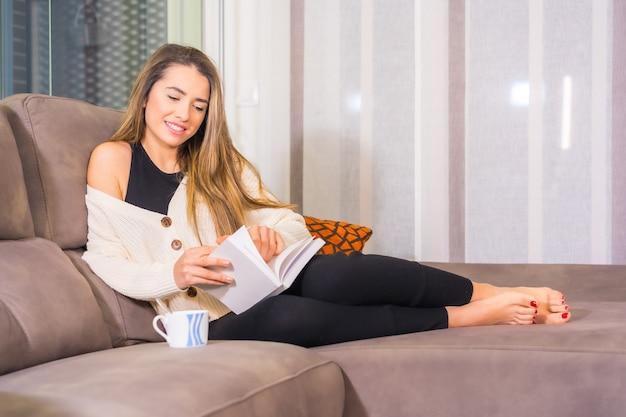 Estilo de vida em casa, jovem loira caucasiana com um café sorrindo, lendo um livro no sofá da sala de estar