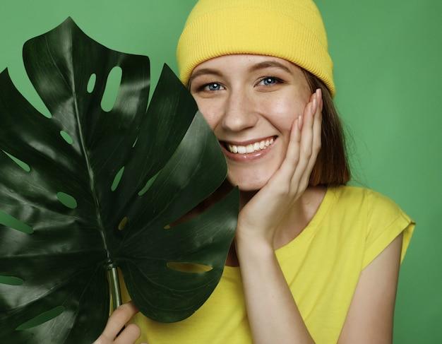 Estilo de vida, emoção e conceito de pessoas: mulher bonita sorridente por trás da folha grande