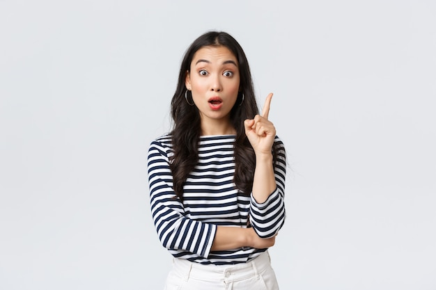 Estilo de vida, emoções das pessoas e conceito casual. colega de trabalho asiática inteligente e criativa animada tem sugestão, adicionar ideia, levantando o dedo indicador para dizer o pensamento ou plano, fundo branco de pé.