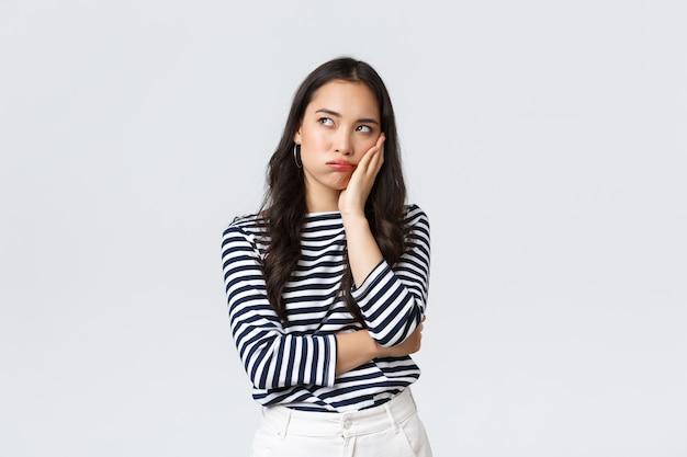 Estilo de vida, emoções das pessoas e conceito casual. mulher asiática relutante irritada em pé entediada e desapontada com a festa, apoiando-se na palma da mão e olhando para cima, irritada, fundo branco