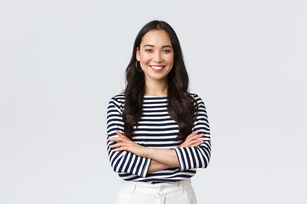 Estilo de vida, emoções das pessoas e conceito casual. mulher asiática sorridente confiante e bonita com os braços cruzados, confiante, pronta para ajudar, ouvindo colegas de trabalho, participando da conversa
