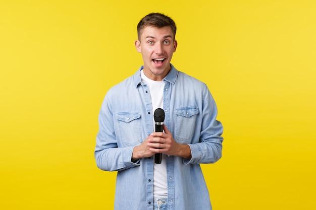Estilo de vida, emoções das pessoas e conceito de lazer de verão. homem loiro bonito feliz animado olhando para longe e sorrindo, falando no palco, apresentar-se ou cantar no karaokê com microfone.