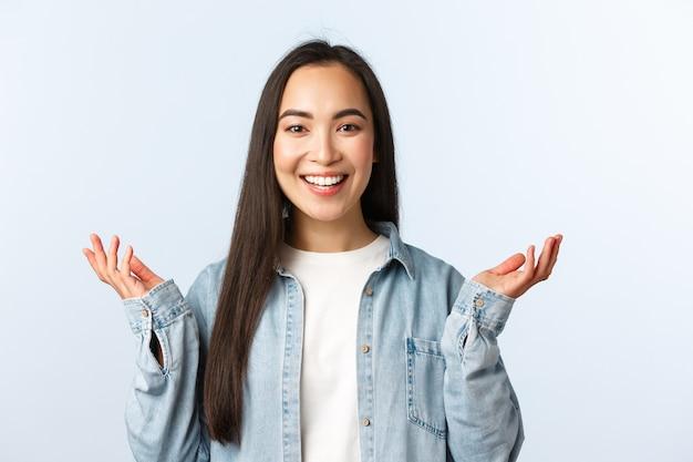 Estilo de vida, emoções de pessoas e conceito de beleza. menina asiática animada surpresa em roupa casual, levantando as mãos e rindo de algo inesperado e agradável, recebe uma boa notícia.