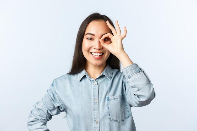 Estilo de vida, emoções de pessoas e conceito de beleza. menina asiática sorridente otimista olhando através de sinal de tudo bem feliz, garantir que tudo esteja sob controle. tudo bem, recomende o melhor produto