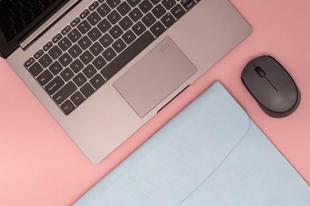Estilo de vida espaço de trabalho para estudante, trabalhador de escritório, freelancer. conceito de educação moderna. laptop cinza na caixa azul e mouse sem fio na vista superior rosa. postura plana.
