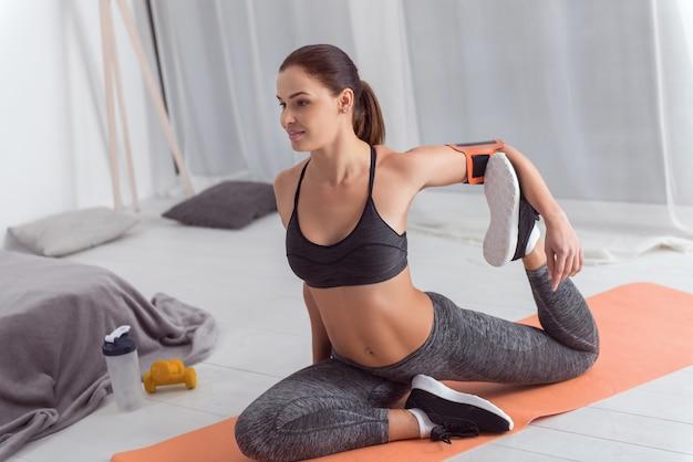 Estilo de vida esportivo. mulher jovem de cabelos escuros, atraente e bem construída, sorrindo e se exercitando sentada no tapete