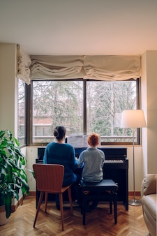 Estilo de vida familiar, passar algum tempo juntos dentro de casa. crianças com virtude musical e curiosidade artística. mãe ensinando seu filho em casa aulas de piano.