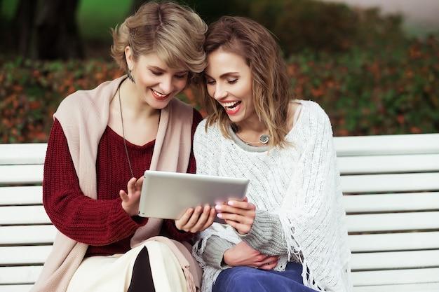 Estilo de vida, felicidade, conceito emocional e de pessoas: belas mulheres meninas outono usando tablet ao ar livre