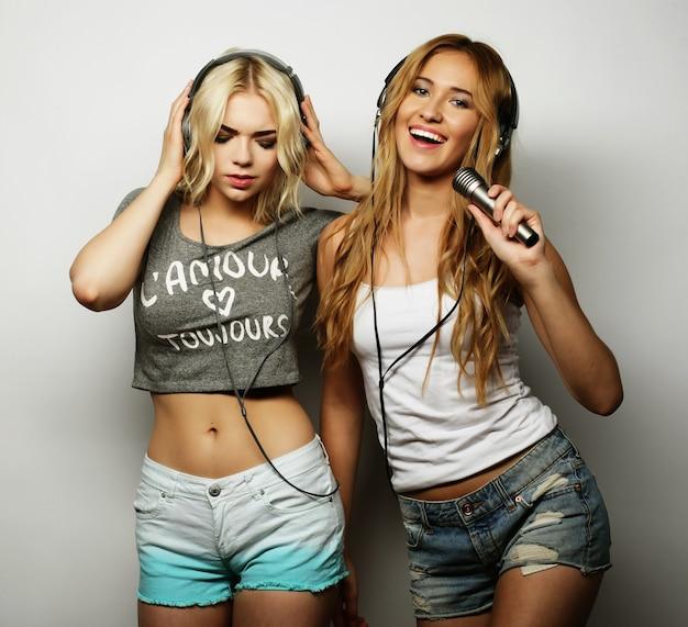 Estilo de vida, felicidade, conceito emocional e de pessoas: garotas bonitas e hipster com um microfone cantando e se divertindo