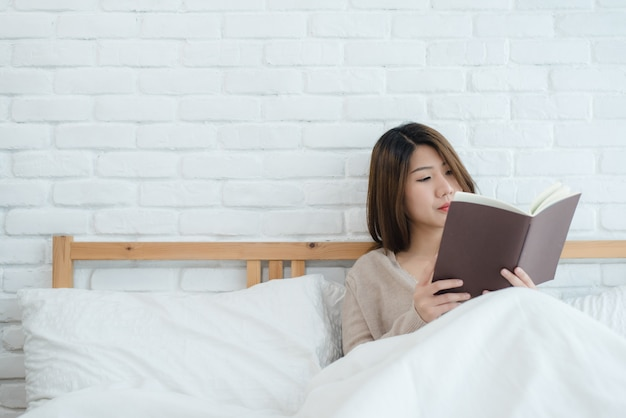 Estilo de vida feliz jovem mulher asiática desfrutando deitado na cama lendo livro prazer em roupas casuais