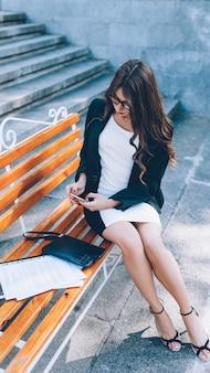 Estilo de vida feminino. carreira de sucesso. mulher de negócios confiante, sentado no banco com os papéis do telefone.