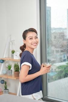 Estilo de vida feminino misto atraente tomando uma xícara de chá, olhando pela janela