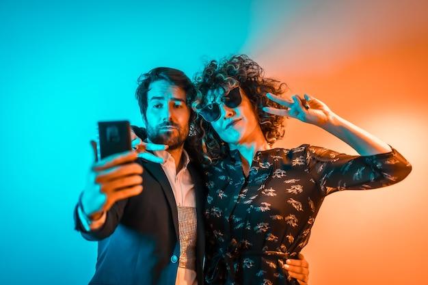 Estilo de vida festeiro, um casal caucasiano tirando uma selfie em uma festa com luzes laranja e azuis