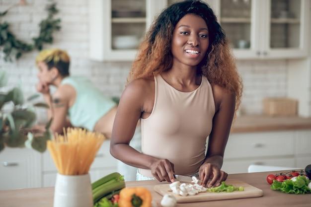 Estilo de vida. jovem americana alegre com um sorriso cheio de dentes, preparando comida de vegetais e uma namorada caucasiana no fundo da sala